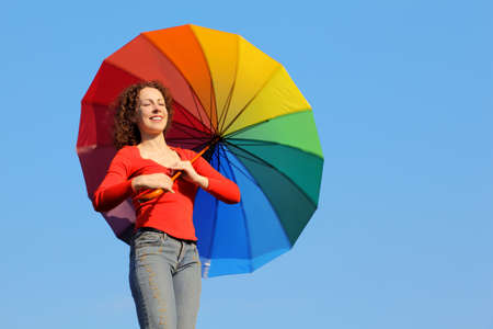 Girl with eyes closed because of glare of sun stands against blue sky and holding colored umbrella photo