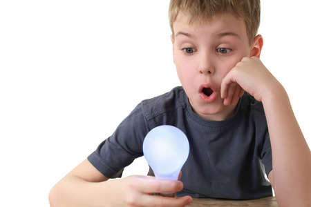 Boy holds plug in  lamp and in surprise looks at it Stock Photo