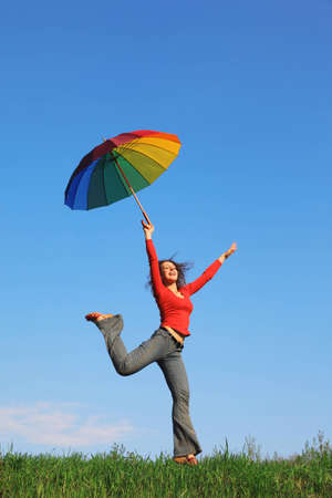 Girl jumping over green grass with colorful umbrella in his hand against blue sky Stock Photo - 12646703