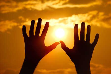 オレンジ色の夕日に対する手のシルエット。クローズ アップ。