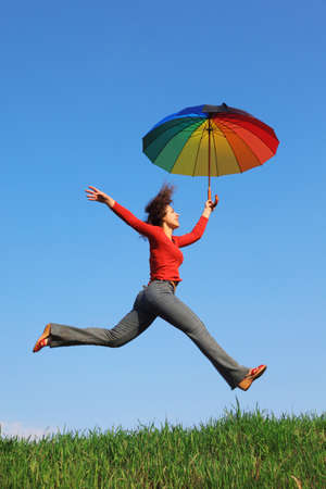 beautiful umbrella: Girl jumping over green grass with colorful umbrella in his hand against blue sky