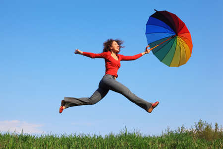 Girl jumping over green grass with colorful umbrella in his hand against blue sky