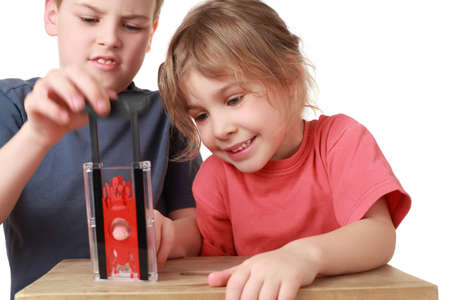 guillotine: Brother and sister play with  little guillotine, focus on sister