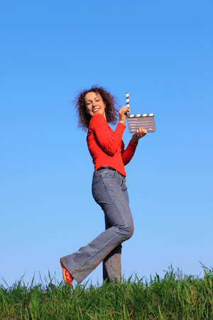 girl stands in meadow with green grass against blue sky and keeps clapperboard photo