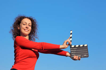 Smiling girl standing against the blue sky and keeps in his outstretched hands clapperboard Stock Photo - 12646632