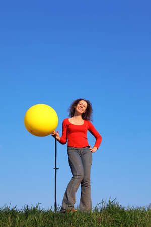 Girl stands in meadow with green grass against blue sky and inflates with foot pump yellow balloon photo