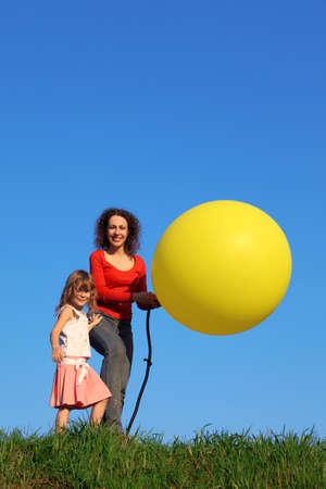 Mother and daughter stand in meadow with green grass against blue sky, one of which inflates yellow balloon with pump, while other keeps ball in his hands photo