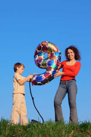 Mother and son standing in meadow with green grass on blue sky background and holding an inflatable figure of nine photo