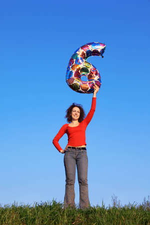 Girl stands in meadow with green grass against blue sky and holds in his outstretched arm above his head inflated figure of six photo