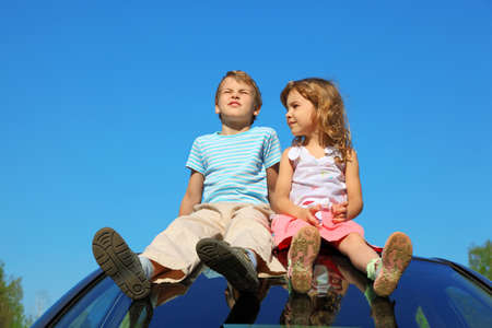 little boy and girl sitting on car roof on blue sky photo