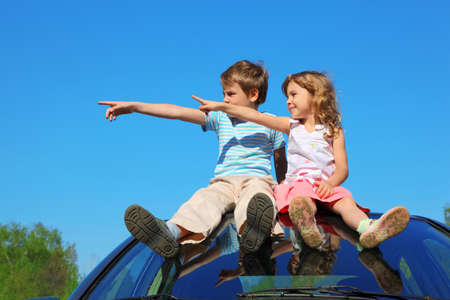 little boy and girl sitting on car roof on blue sky, looking to left side and showing by finger 스톡 콘텐츠