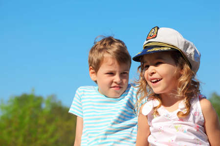 little girl with captain cap and boy at sunny day photo