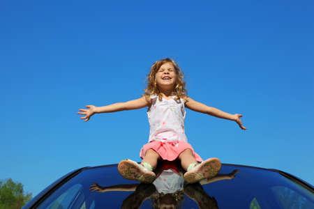 gambe aperte: bambina seduta sul tetto della vettura con le mani aperte sul cielo blu