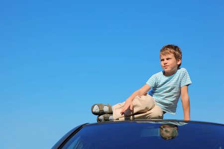 niño modelo: chico serio sentado en el techo del coche, el cielo azul Foto de archivo