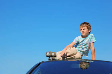 child model: serious boy sitting on roof of car, blue sky