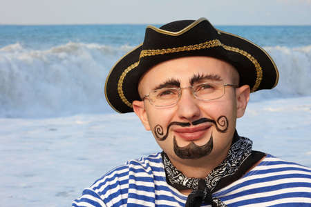 sailor hat: portrait of smiling man with drawed beard and whiskers in pirate suit. sea wave in out of focus.