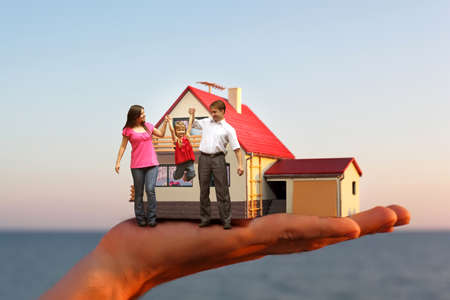 model of house with garage on hand against sea and family with girl collage 스톡 콘텐츠