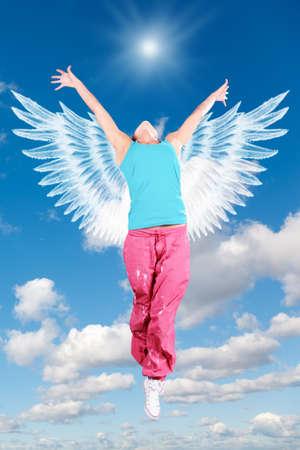 angel bailando mujer con alas en ropa deportiva salta en cielo collage Foto de archivo