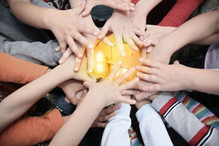 team power: Children have combined hands together to miniature house collage Stock Photo