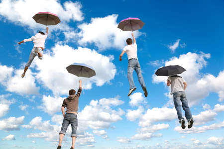 behind flying four friends with umbrellas on White, fluffy clouds in blue sky collage Standard-Bild