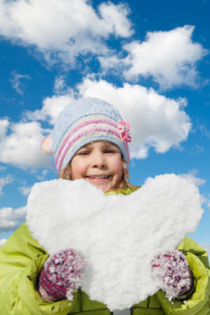 keeps: smiling little girl keeps in hands snow hearts on winter sky collage