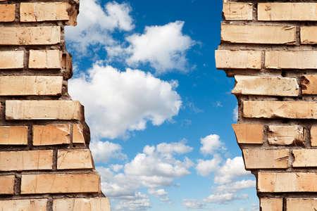 ひびの入った煉瓦壁と青い空をコラージュします。 写真素材