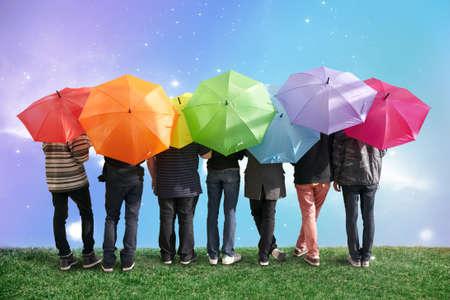 草原のコラージュに虹色の傘を持つ 7 人の友人