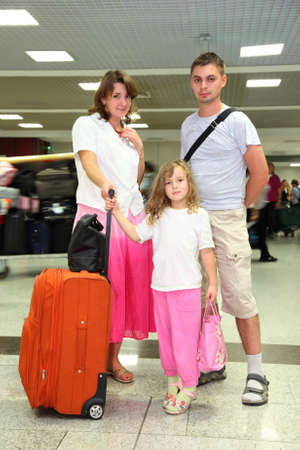 young mother, father and little daughter with baggage at the airport photo