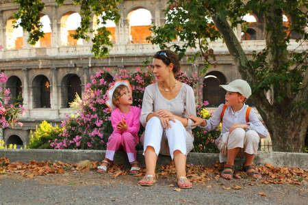 young mother, little son and daughter sitting near Colosseum in Rome and talking, focus on mother 스톡 콘텐츠