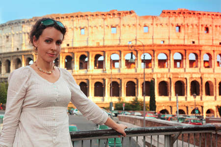 beautiful young woman in white wear standing on bridge near Colosseum at summer day  photo
