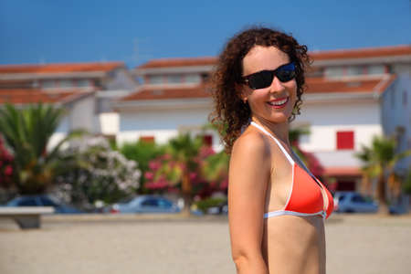 mandatoriccio: beautiful young woman in red swimsuit and sunglasses stands on beach