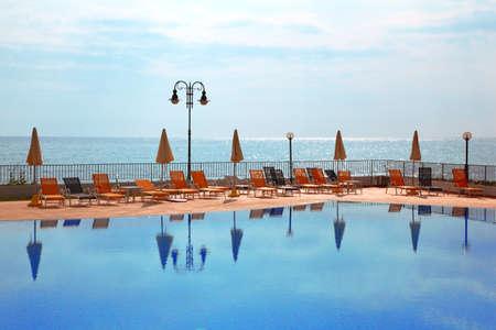 mandatoriccio: few orange loungers and parasol standing near to open pool, sea