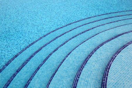 mandatoriccio: steps into pool, pure, transparent water, blue tiles on bottom of pool Stock Photo