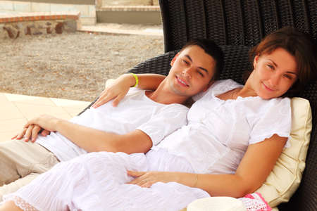 young husband and wife in white dress sitting on black wicker chair and hug photo