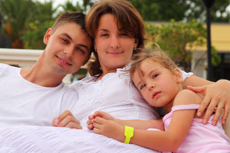 young husband and wife and daughter sitting and hug, focus on little girl  photo