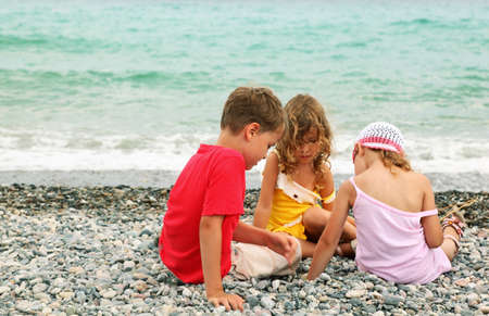 Pebble Beach: little brother and two sisters are sitting on beach and play. coast Stock Photo