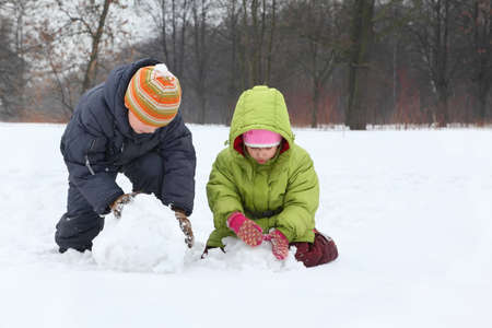 sculpt: Brother and sister sculpt snowman in street in winter Stock Photo