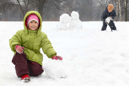 sculpt: Two children play on outdoor in winter and sculpt snowman, focus on girl