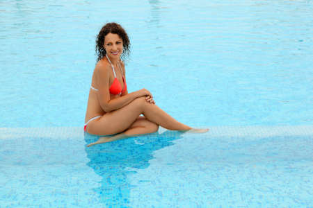 mandatoriccio: beautiful young woman in red bathing suit sitting in pool. Blue clear water Stock Photo