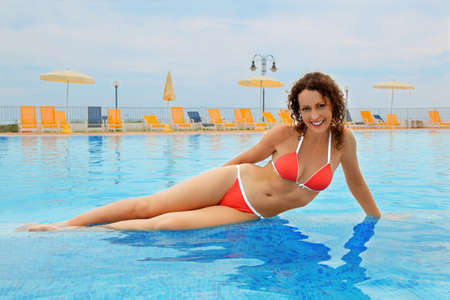 mandatoriccio: beautiful young woman in red bathing suit sitting in pool. yellow chairs and beach umbrellas