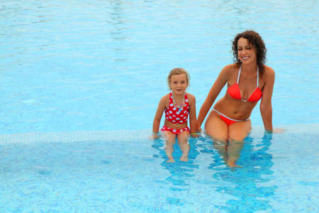 beautiful young mother in red bathing suit and her daugther sitting in open pool, focus on mother