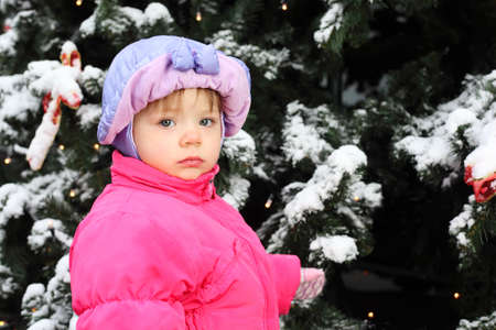 child ball: Little girl dressed pink jacket stands near green tree with snow Stock Photo
