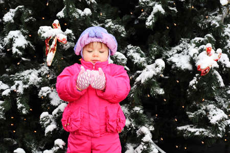 Little smiling girl dressed pink jacket stands near green tree with snow and holds snow Stock Photo - 17751847