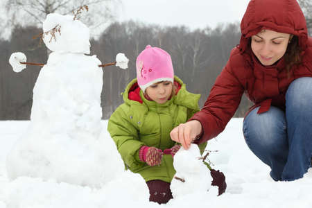 Mother and girl in winter on outdoor sculp little snowman Stock Photo - 17722794