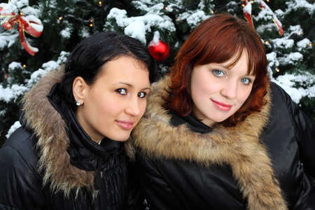 Two young women stands near green tree with snow; two friends photo