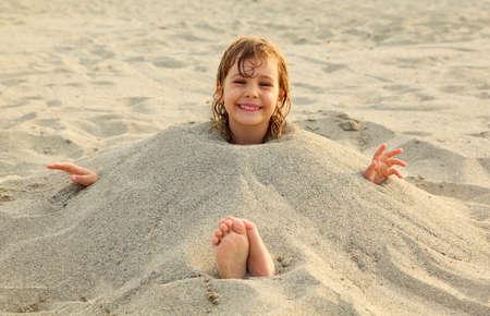 水泳の後の女の子は多くの黄色の砂のビーチの砂に埋葬されました。