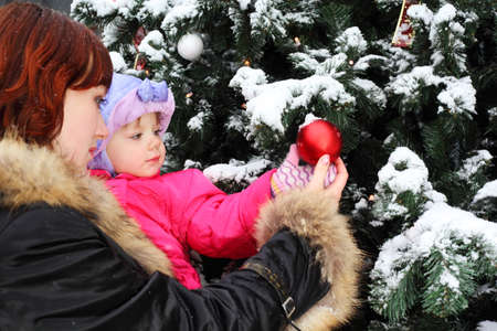 Young woman with small daughter stands near green tree with snow and touch red ball photo