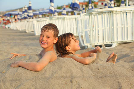 little brother and sister buried in sand on beach, rows of white deck chairs and beach umbrellas