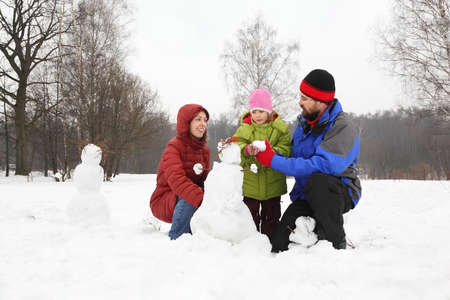 Family from three persons plays in park in winter and sculp snowman photo