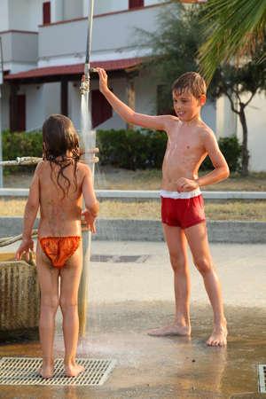 personas tomando agua: peque�o hermano y hermana se toma la ducha al aire libre despu�s de nadar, se centran en ni�o Foto de archivo